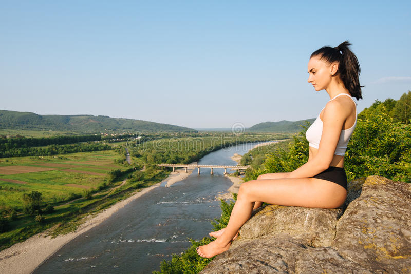 Woman fitness instructor with muscular body relaxing outdoor in beautiful mountains landscape. Meditation and Relax.  royalty free stock photo