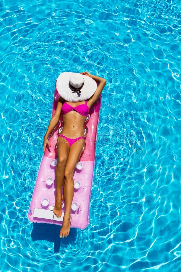 Woman on a float in the pool. Woman takes a sunbath on a float in the pool, aerial shot royalty free stock photo