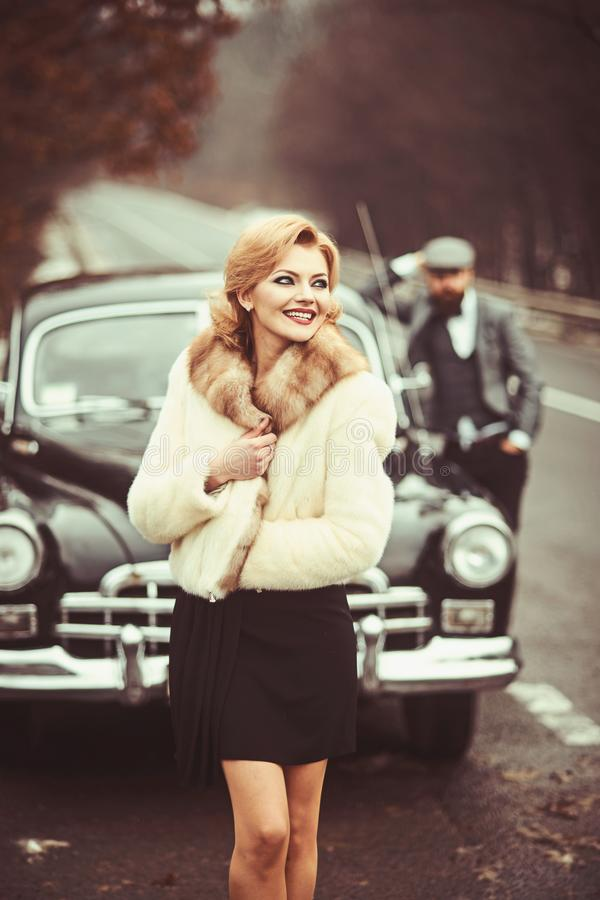 Sexy woman in fur coat and bearded man. Retro collection car and auto repair by mechanic driver. Travel and business royalty free stock image