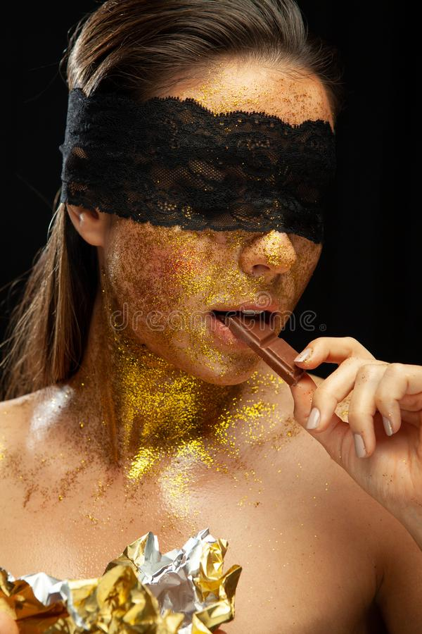 Sexy woman with gold makeup and lace mask, eating chocolate stock images