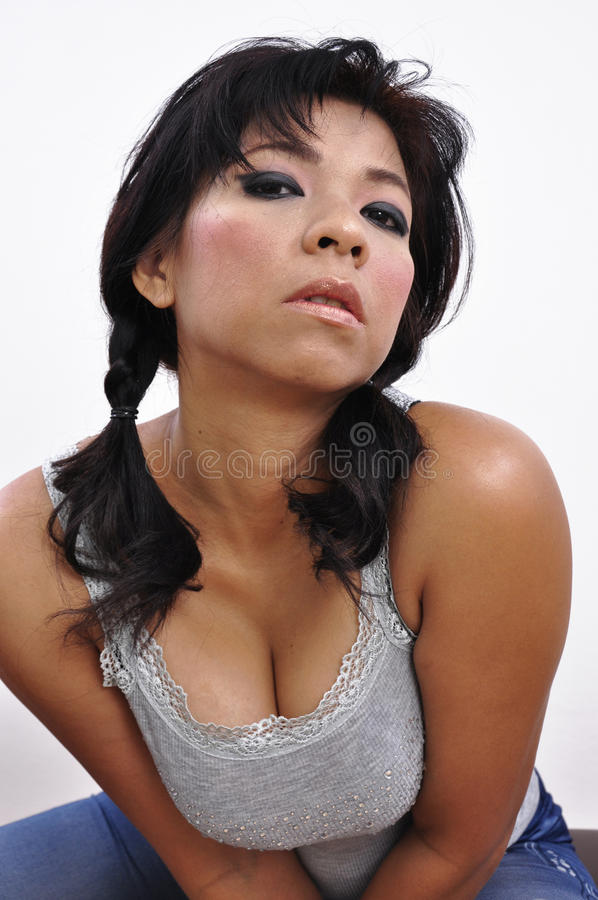 Woman grey top shows generous cleavage. Isolated Asian woman grey top showing generous cleavage, faces the camera on white background stock images