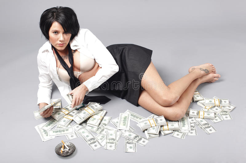 Woman handling lots of cash. Woman with loose clothing handling lots of cash and smoking a cigarette royalty free stock images
