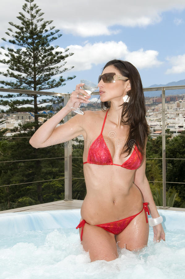 Woman having a drink in outdoor jacuzzi stock images