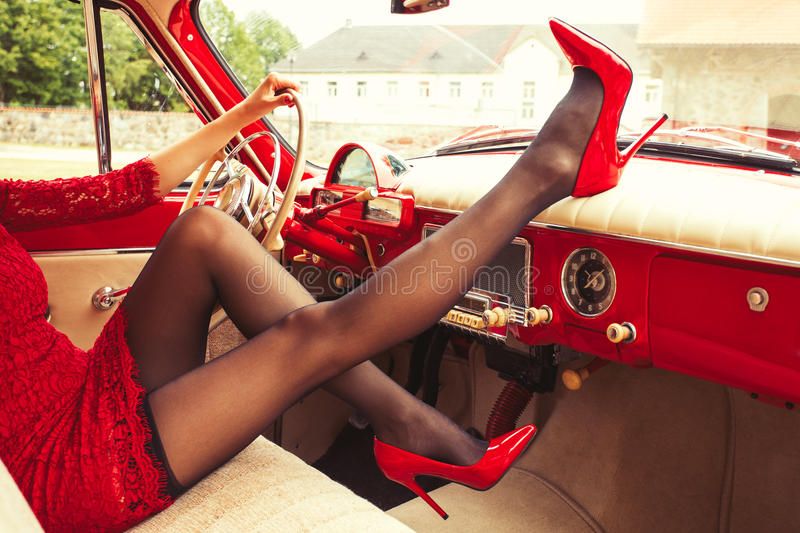 woman in high-heals sitting in retro car stock photo