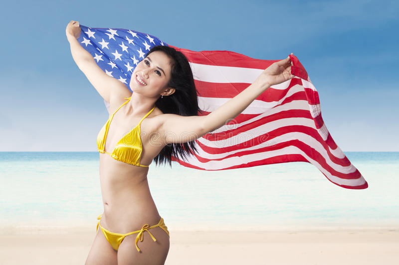 Woman holding american flag at beach. Young beautiful happy woman holding american flag enjoying summer time at beach stock photos