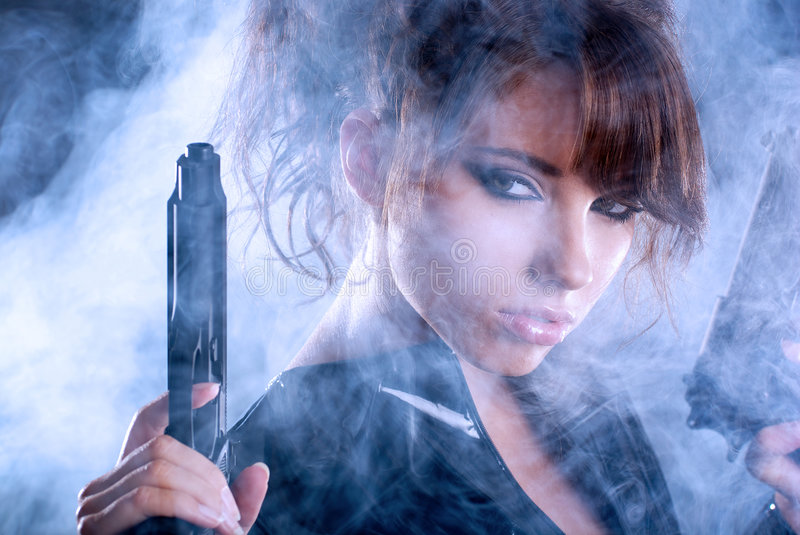 woman holding gun with smoke stock images
