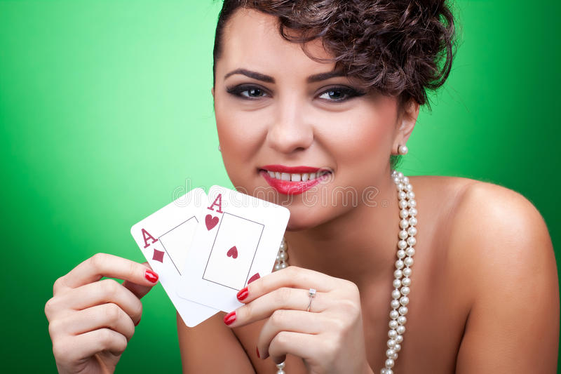 woman holding a pair of aces stock photography