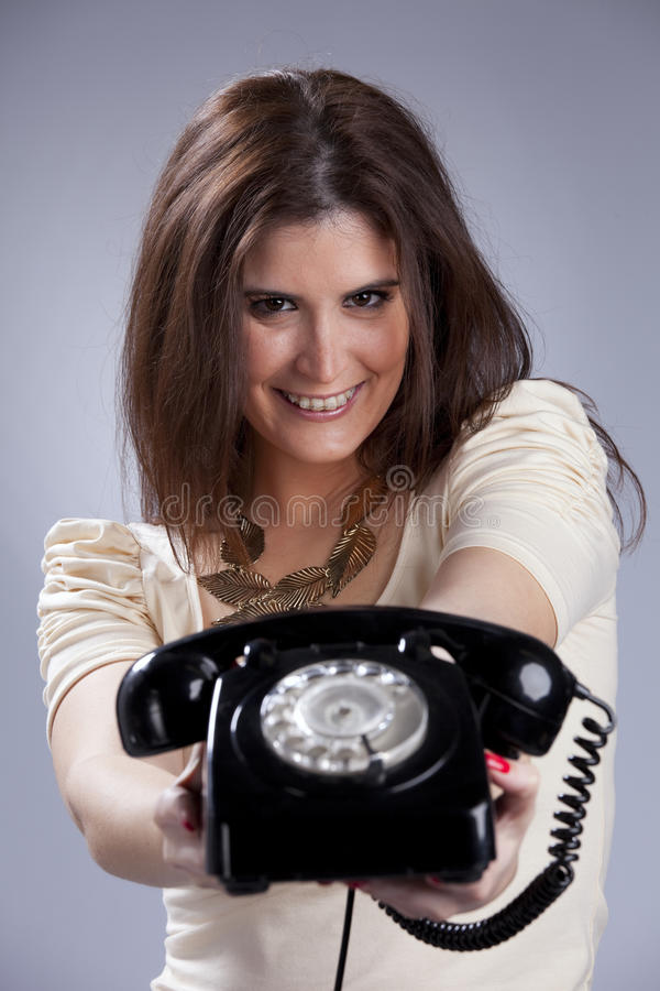 Woman holding a telephone. Happy woman holding a telephone stock image