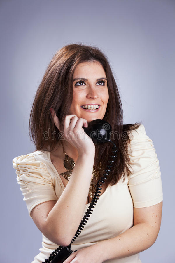 Woman holding a telephone. Happy woman holding a telephone royalty free stock images