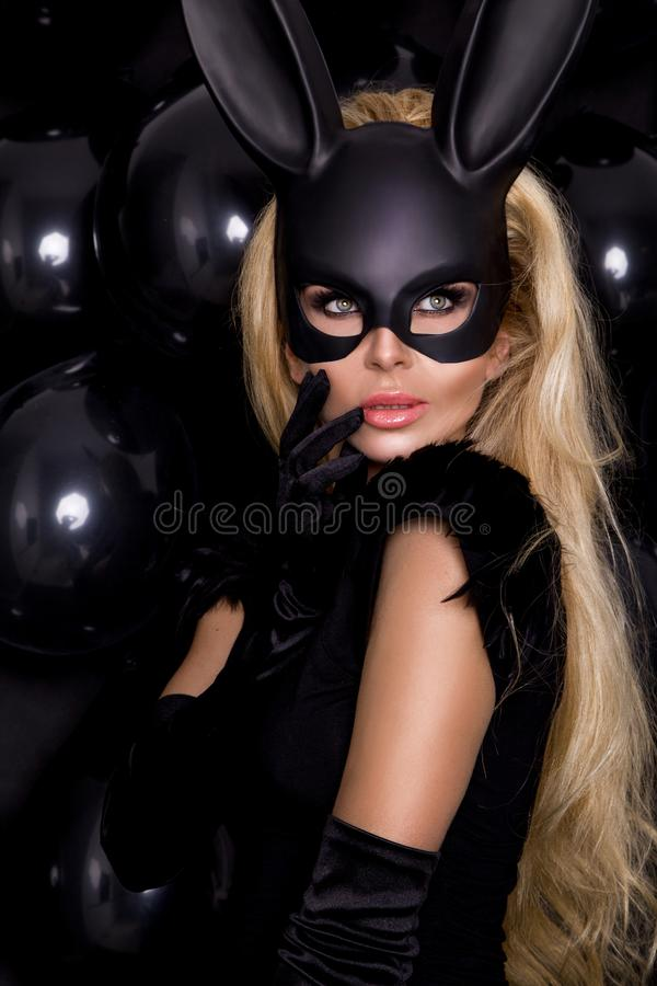 woman with large breasts, wearing a black mask Easter bunny stock image