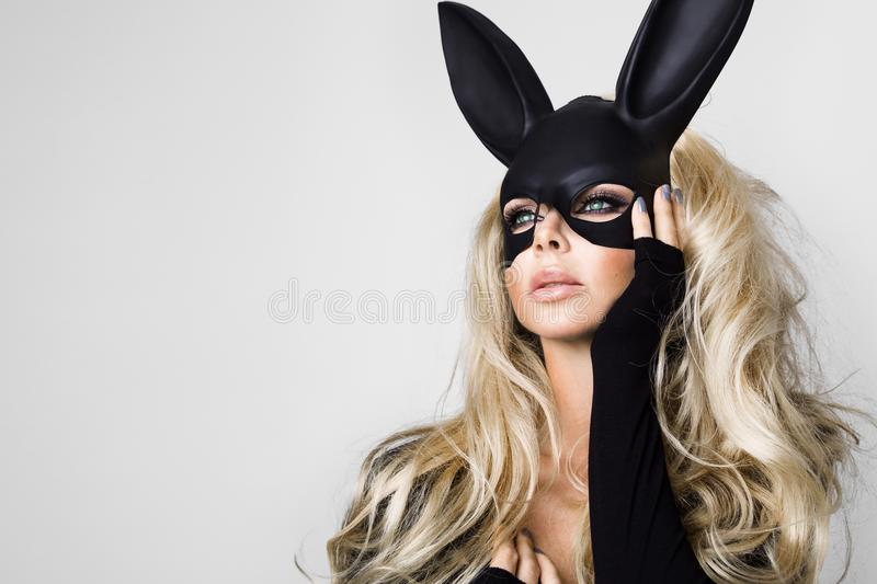 Woman with large breasts wearing a black mask Easter bunny standing on a white background. And looks very sensually royalty free stock image