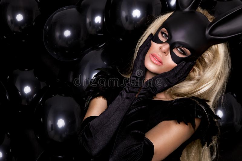 Woman with large breasts, wearing a black mask Easter bunny. Standing on a white background and looks very sensually royalty free stock photos