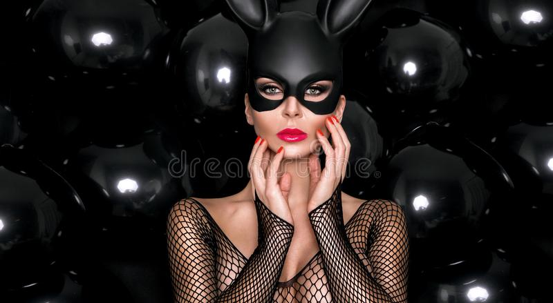 Woman with large breasts, wearing a black mask Easter bunny. Standing on a white background and looks very sensually stock image