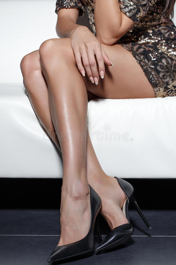 Woman legs in stiletto high heels. Sitting on sofa stock photography