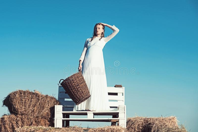 woman with long blond hair. Albino girl hold wicker basket with hay on sunny outdoor picnic. Woman bride in wedding stock photos
