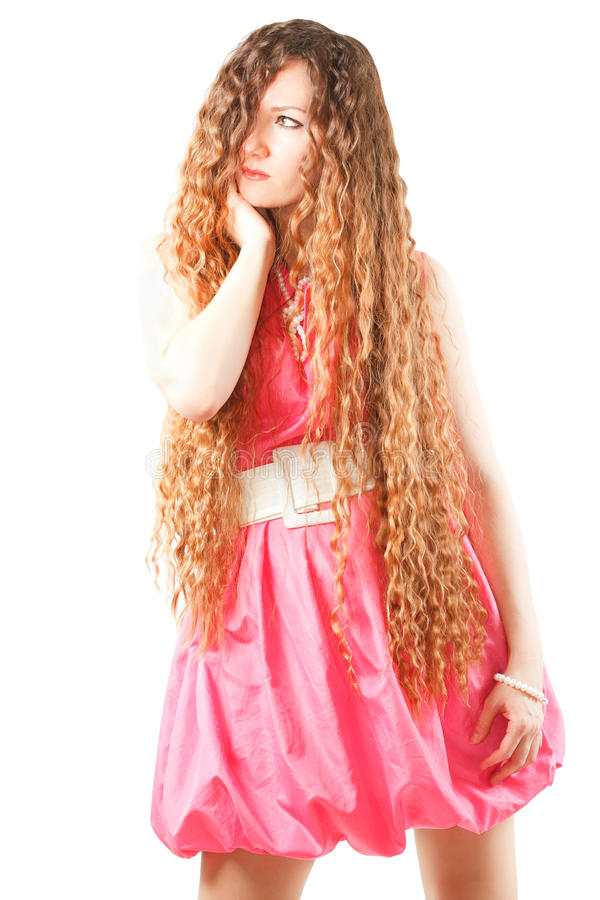 Woman with long curly hair in pink dress. Beautiful woman with long curly hair in pink dress on white background More of this series on my portfolio royalty free stock images