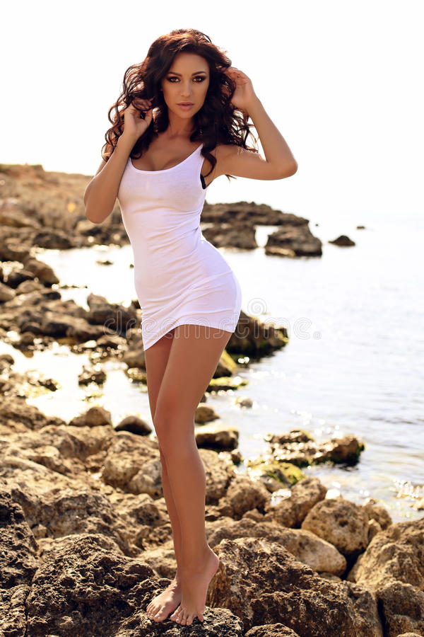 Woman with long dark curly hair wearing bikini and beach cl. Fashion outdoor photo of gorgeous woman with long dark curly hair wearing bikini and beach clothes royalty free stock photography