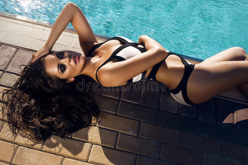 woman with long hair in bikini relaxing beside a swimming pool stock photography