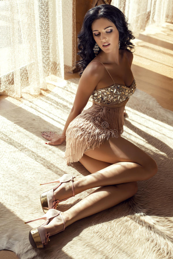 Woman in luxurious dress lying on carpet in room. Fashion photo of beautiful glamour woman with black hair in luxurious dress lying on carpet at bedroom in stock photo