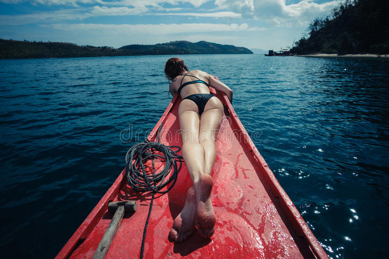 woman lying on boat in the tropics stock photo