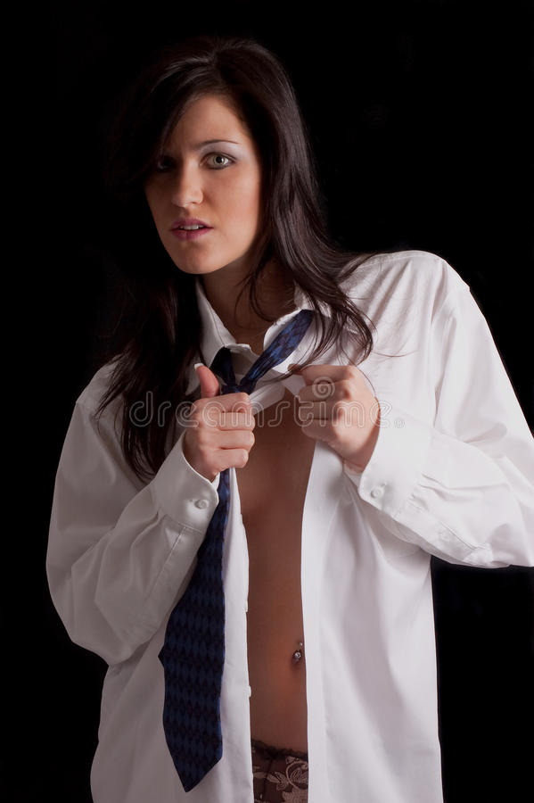 Woman in mans shirt. A studio portrait of a woman unbuttoning the front of a man's shirt she is wearing. Black background stock photos