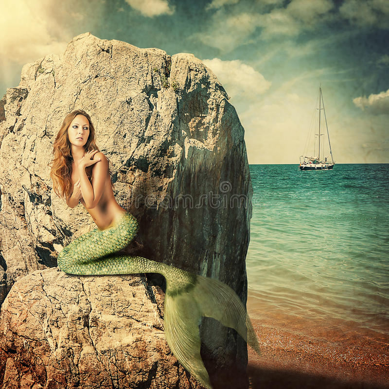 Woman mermaid with long tail. Beautiful woman mermaid with long tail sitting on a rock about sea. Hiding from sailboat royalty free stock image