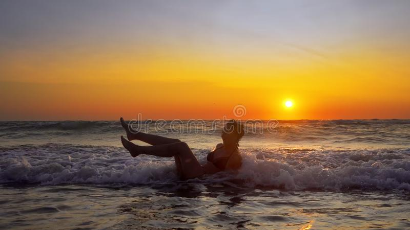 Woman with perfect body sitting in ocean water at sunset. On tropical beach. Cinematic steadicam royalty free stock photos