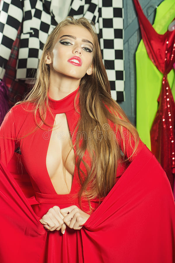 Woman portrait. Portrait of one sexual pretty sensual diva young woman with long hair in red dress with deep low neck standing in wardrobe among many colorful stock photography