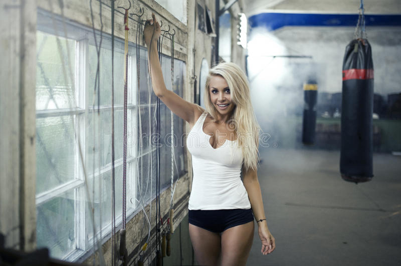 Woman posing in boxing hall. Slim woman training in old hall stock image