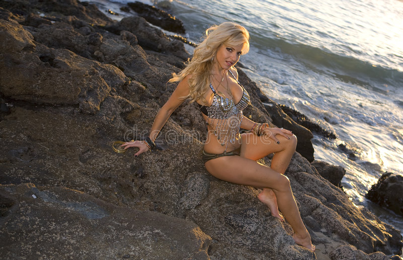 Woman posing on Rocks. Woman in flashy outfit posing on the Rocks stock images