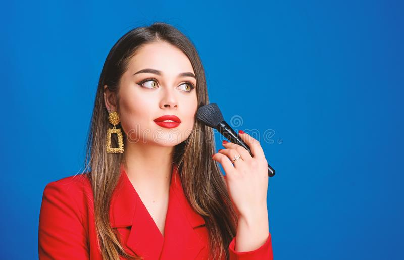 Sexy woman with professional makeup brush tool. jewelry earrings. Girl in red jacket. beauty and fashion. hair beauty royalty free stock photos
