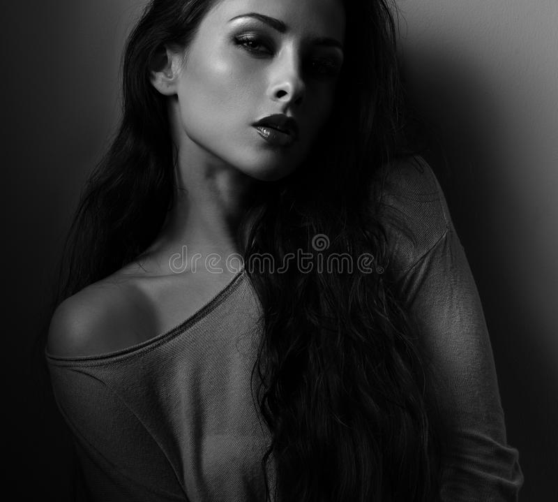 Woman with red lipstick posing in dark shadow black backgro. Und. Closeup portrait stock photography