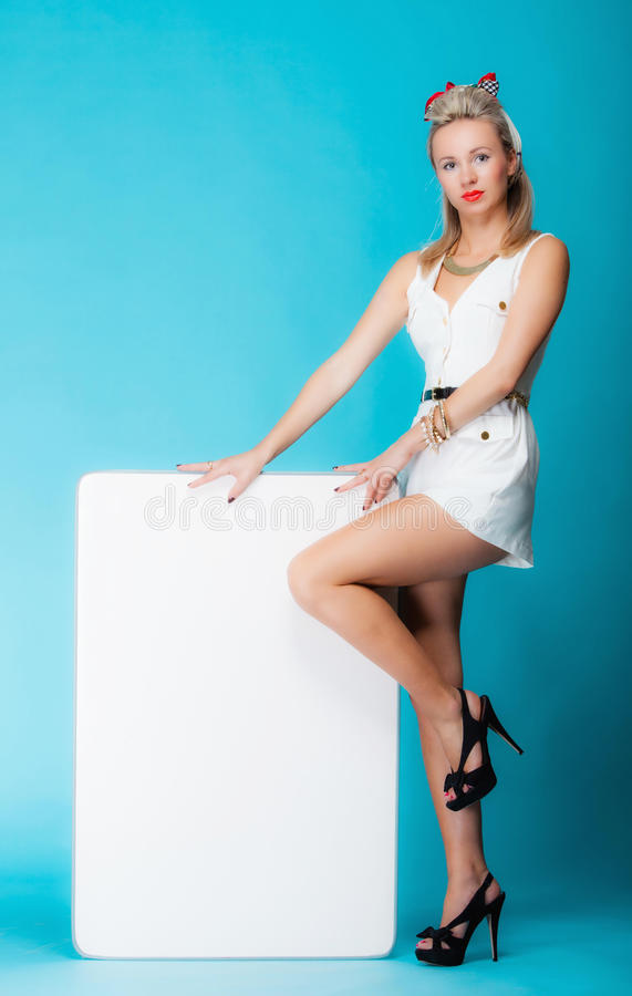 Woman retro style with blank presentation board banner sign. Retro style blonde woman in full length with blank presentation board. Girl holds banner sign royalty free stock photo