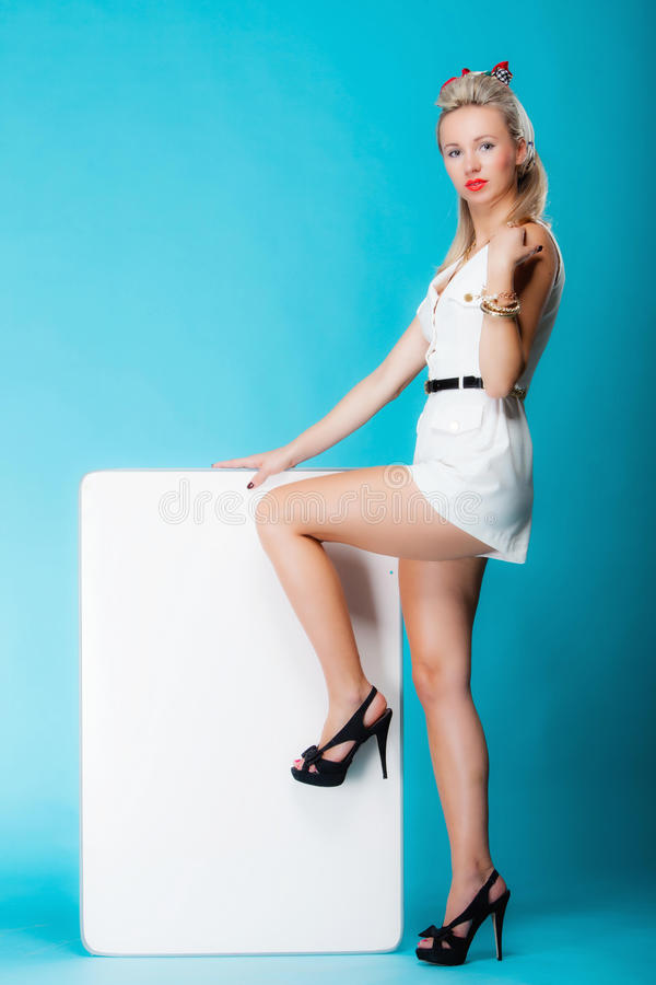 Woman retro style with blank presentation board banner sign. Retro style blonde woman in full length with blank presentation board. Girl holds banner sign royalty free stock images
