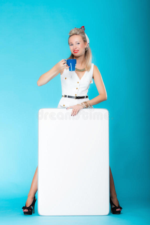 Woman retro style with blank presentation board banner sign. Retro style blonde woman in full length with blank presentation board. Girl holds banner sign royalty free stock photos