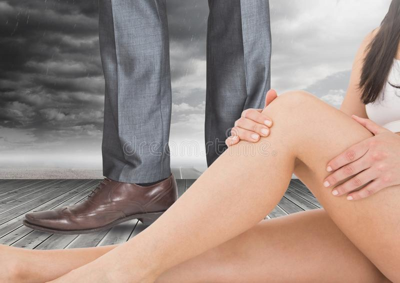 Woman`s legs in front of Man in Business attire`s legs and shoes with clouds. Digital composite of woman`s legs in front of Man in Business attire`s legs and royalty free stock photo