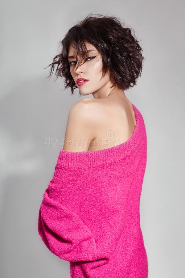 Woman with short hair cut in pink red sweater on white background. Perfect girl with wet tousled dark hair and bright makeup. Short hair, beauty and hair care stock images