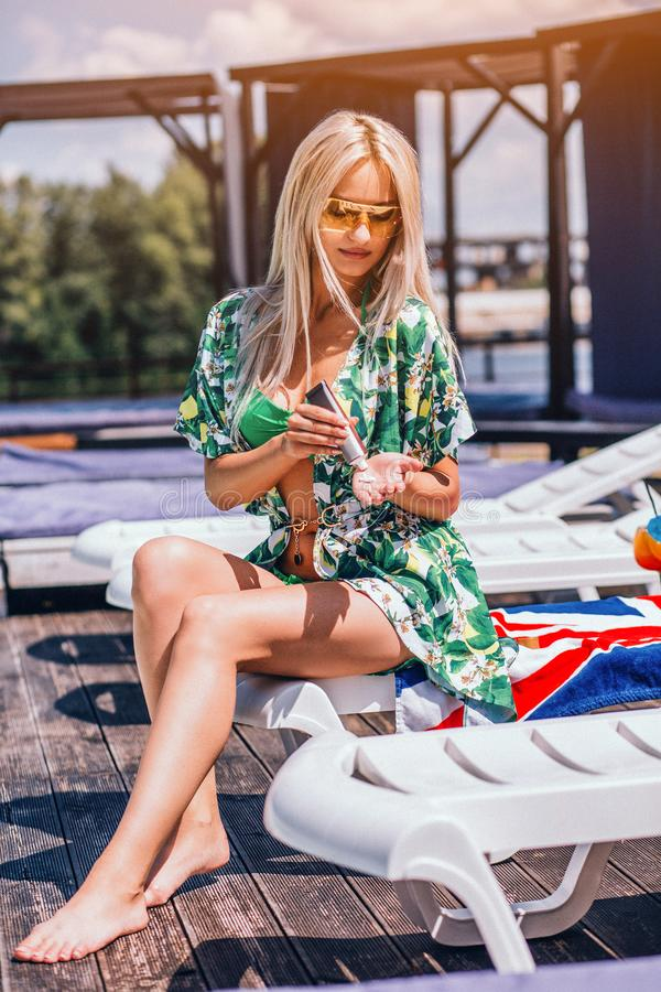 Sexy Woman Is Sitting On The Deck Chair At The Pool In Green Swinning Suit. Sexy Woman Is Sitting On The Deck Chair At The Pool. Young Woman Is Sunbathing In stock image