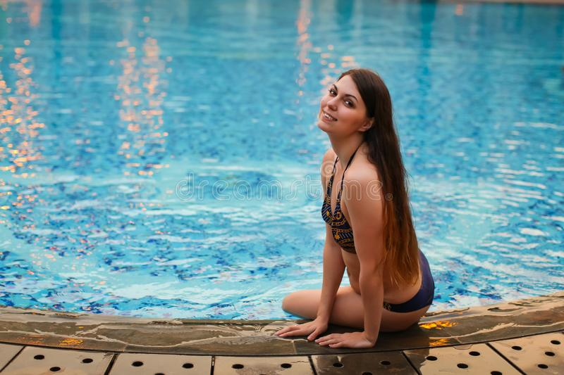 woman sitting on the edge of swimming pool, wearing bikini while on vacations in a sunny tropic destination. stock photo