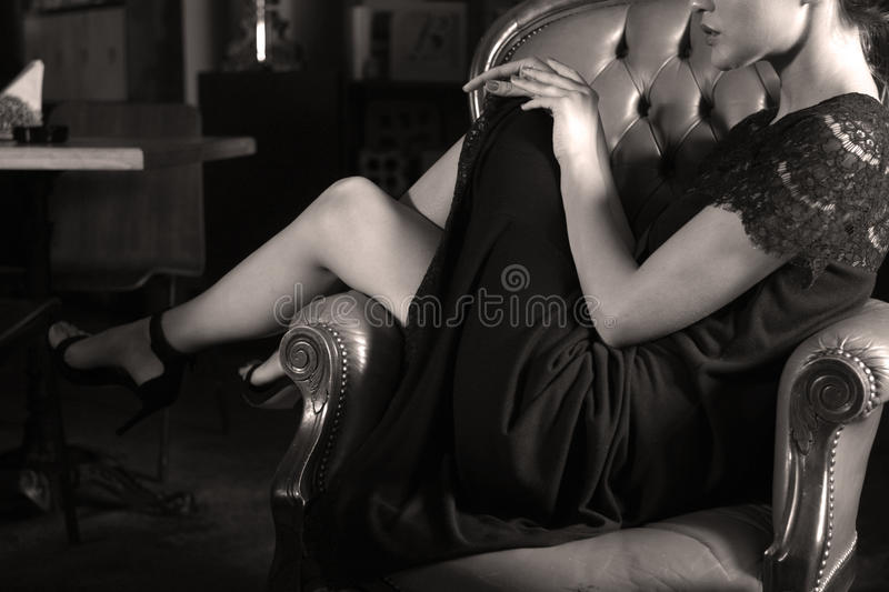 Woman. Sitting on a luxurious armchair royalty free stock image