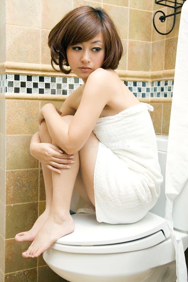 woman sitting on toilet royalty free stock image