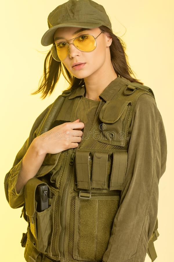 woman in soldier`s suit on yellow background. royalty free stock photos