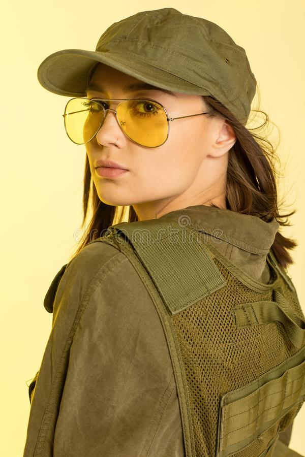 woman in soldier`s suit on yellow background stock photo