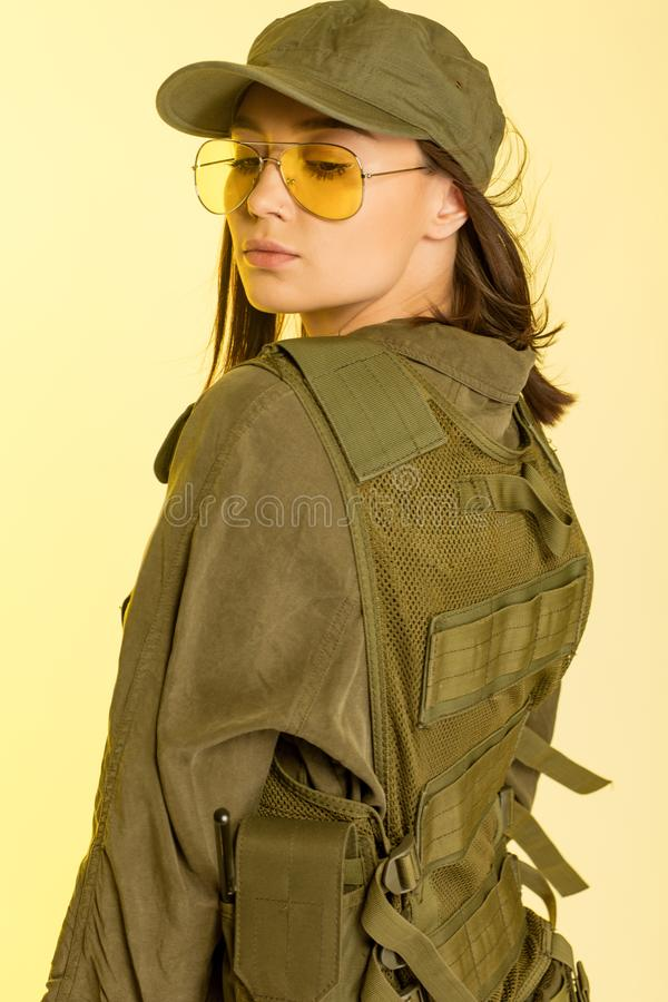 woman in soldier`s suit on yellow background. royalty free stock photography