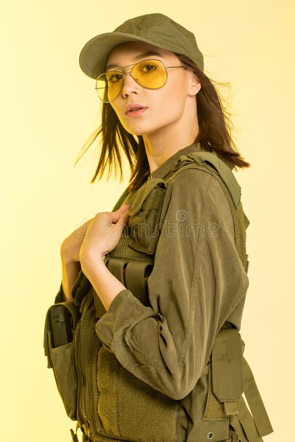 woman in soldier`s suit on yellow background stock images
