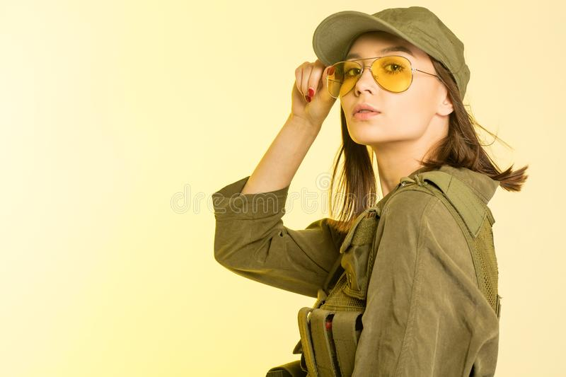 woman in soldier`s suit on yellow background stock image
