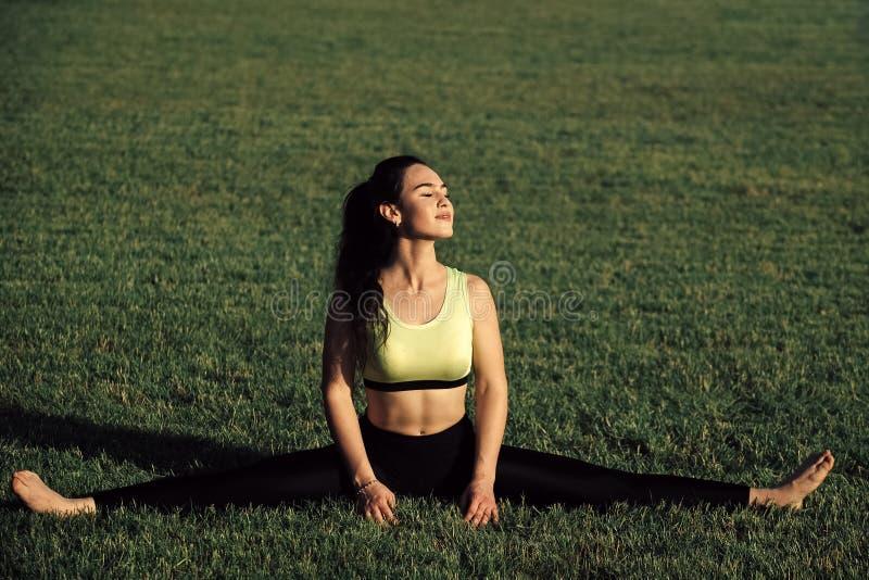 woman stretch legs on green grass, cross split stock image