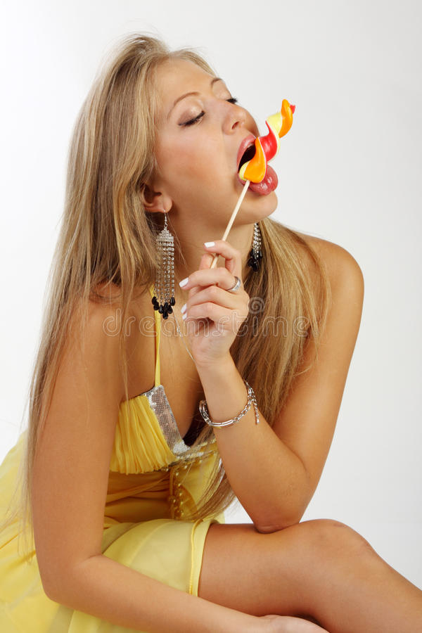 Woman sucks sugar candy. Young woman sucks sugar candy royalty free stock photo