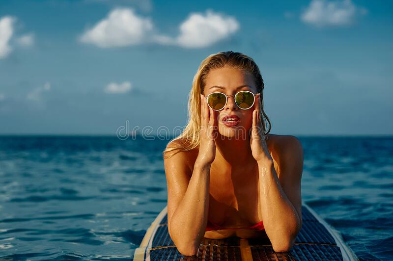 Sexy woman in sunglasses posing, lying on a longboard in the sea royalty free stock image