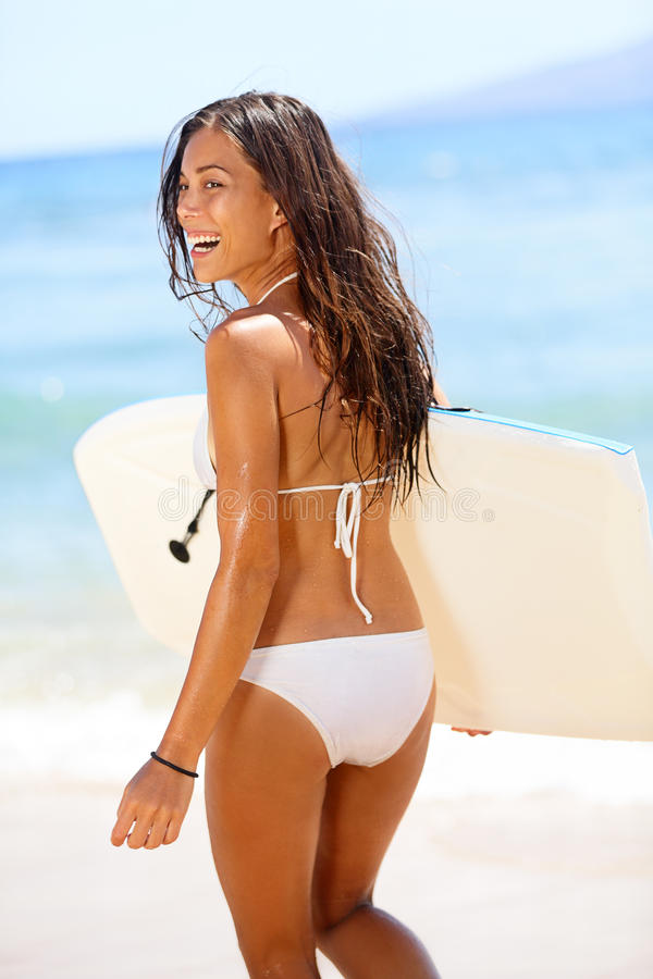 Woman surfer girl body surfing on beach. Beautiful woman laughing having fun bodyboarding under sun and blue sky during summer travel vacation, Maui, Hawaii stock image